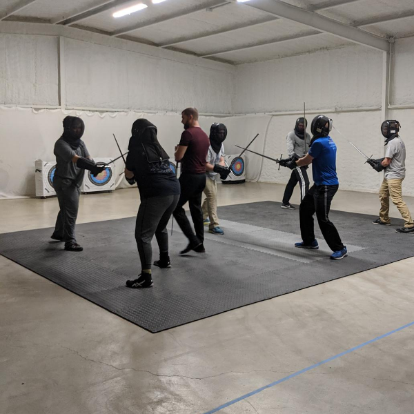 Beginner fight training, instructor leads a group of students with longswords.